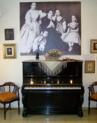 First Albéniz piano. Upper the piano a photo with Albéniz at the age of two with his mother and his sisters. Ensemble into the Isaac Albéniz Museum.